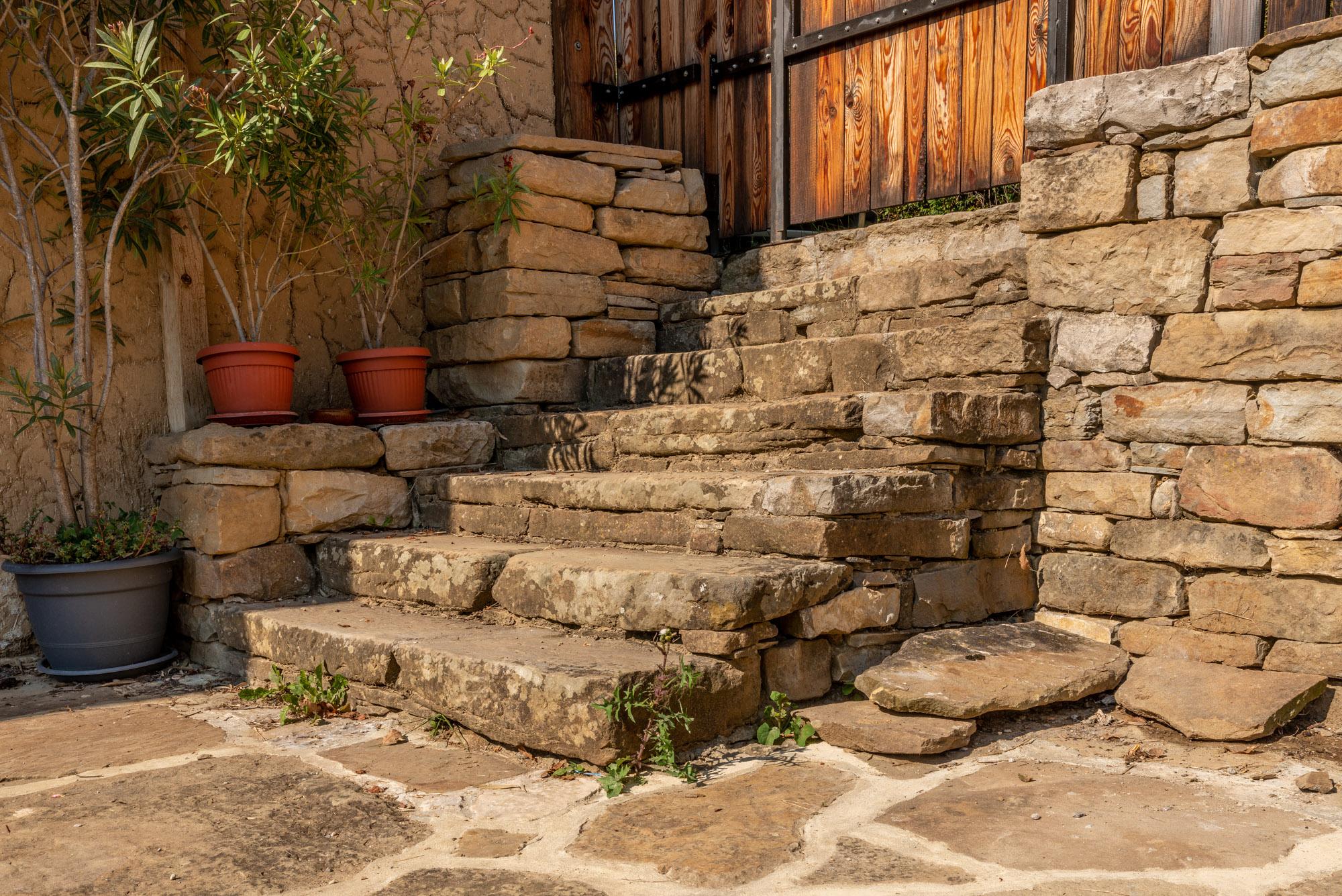 Каменни стъпала, които водят към настилка от естествен камък