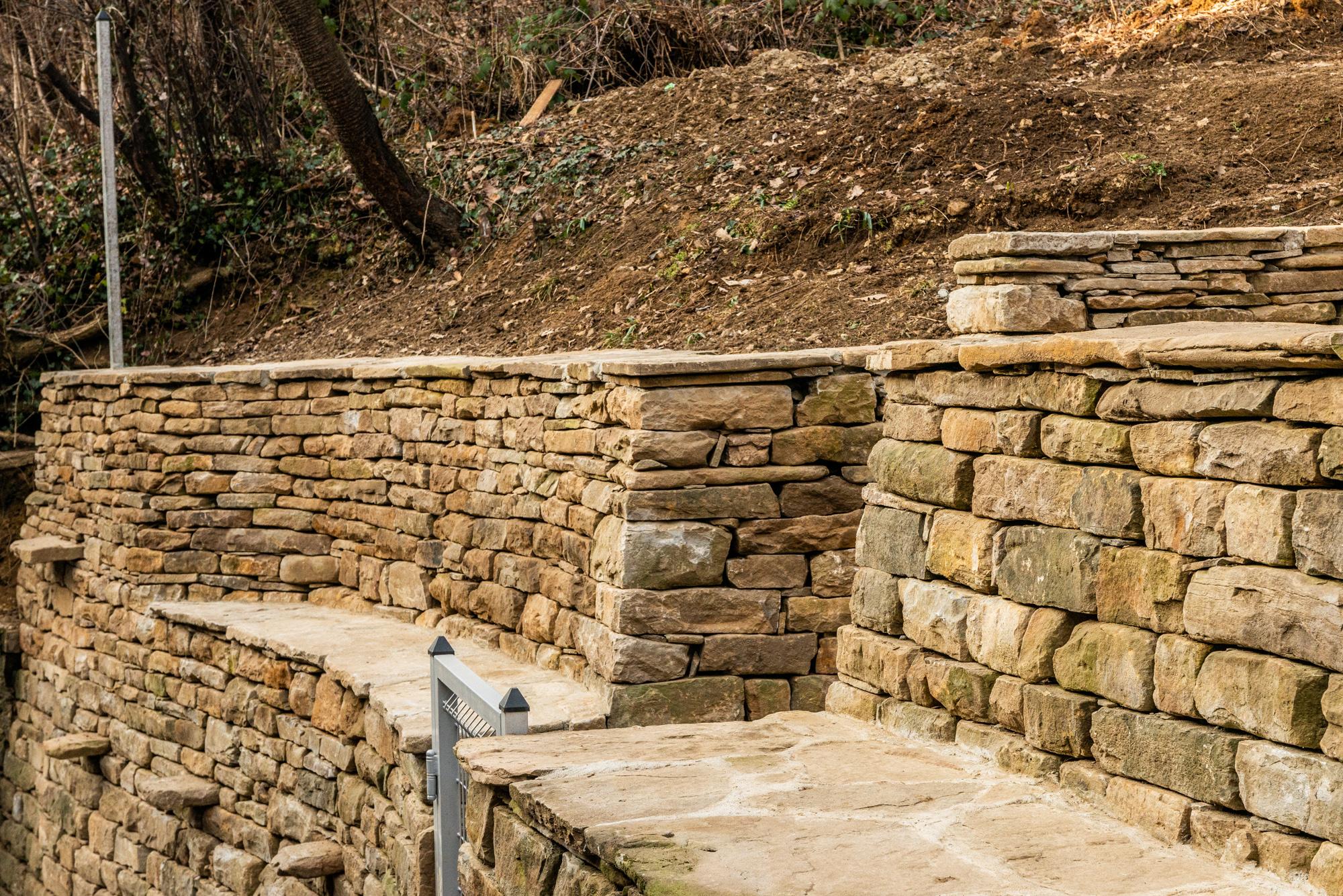 Подпорна стена с междинна площадка, изградена от суха каменна зидария