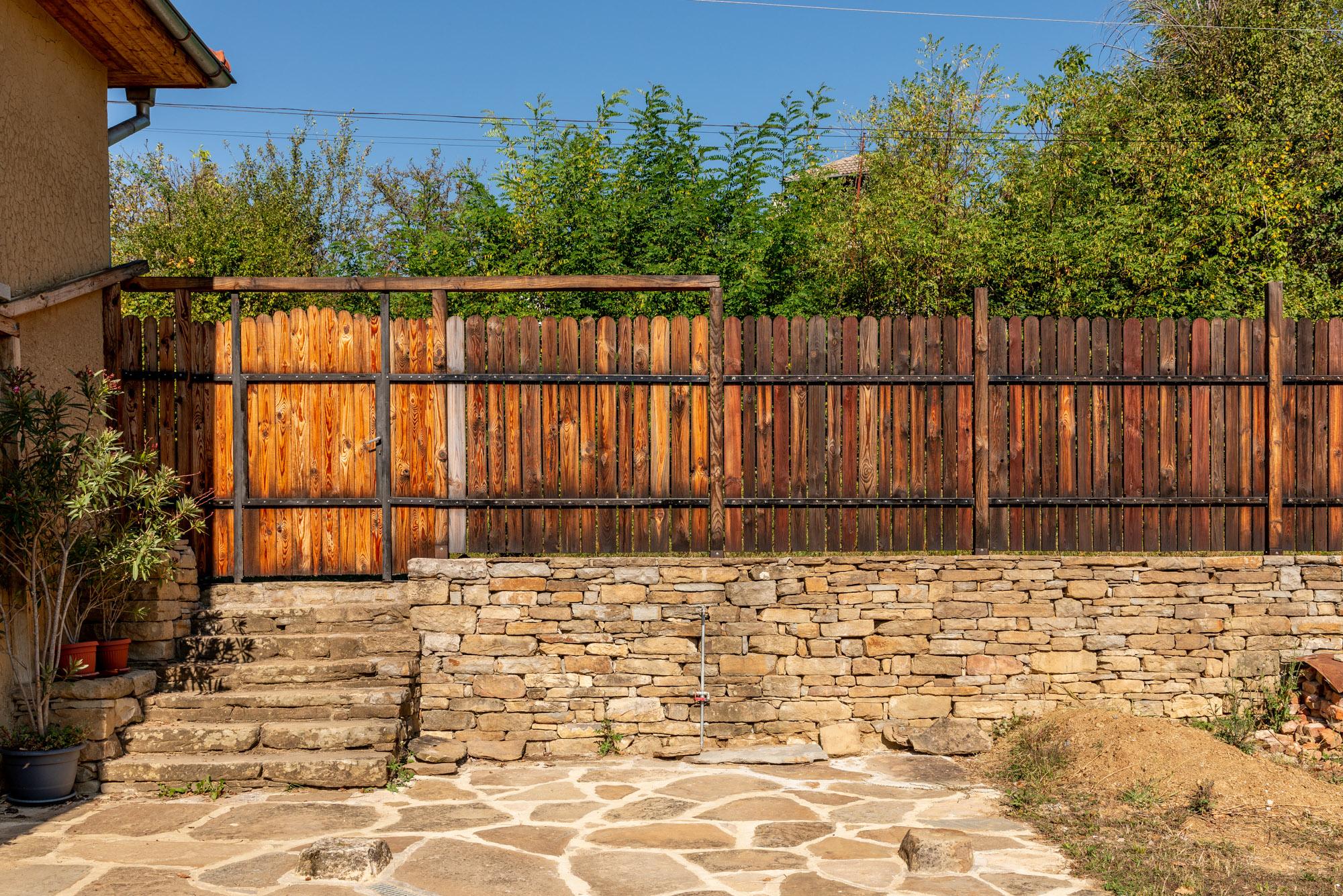Дървена ограда, монтирана върху подпорна стена от суха каменна зидария